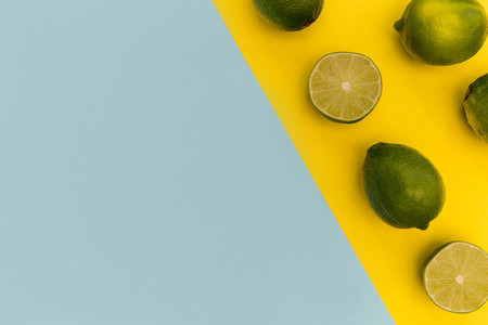 Fresh lime fruits on yellow background summer food concept