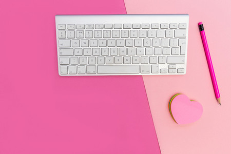 Computer keyboard on pink background minimal workspace concept
