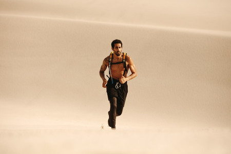 Muscular man running on sand dunes