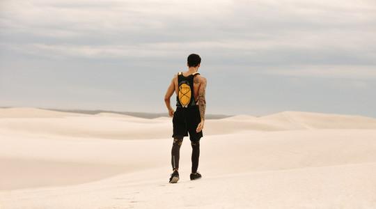 Male athlete walking in desert