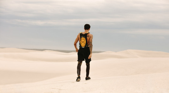 Male athlete walking in desert