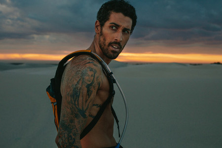 Athlete with hydration pack outdoors at sunset