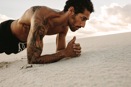 Athlete doing core workout on sand dun