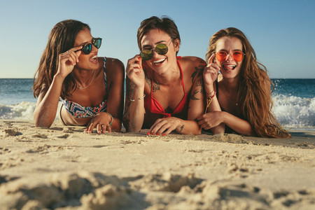 Woman friends sunbathing and enjoying at the beach