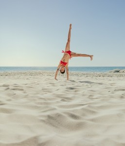 Woman in bikini upside down on beach