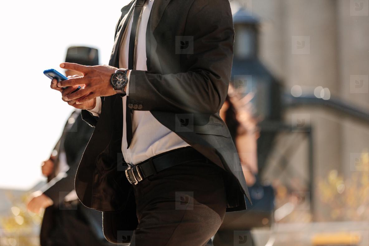 Man using mobile phone while walking on street