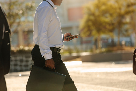 Man using mobile phone while walking on street to office