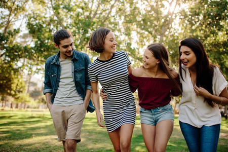 Cheerful friends walking in the park