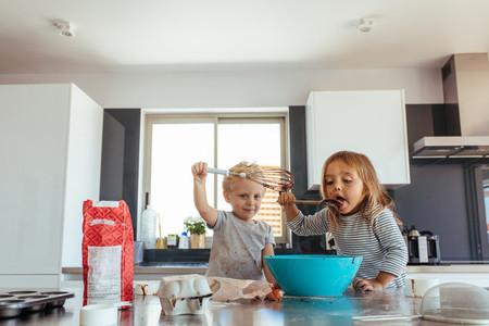 Siblings making cake in kitchen