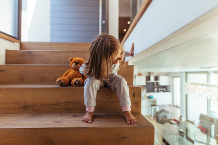 Little girl sitting on staircase at home