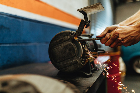 Mechanic grinding a car part on bench grinder
