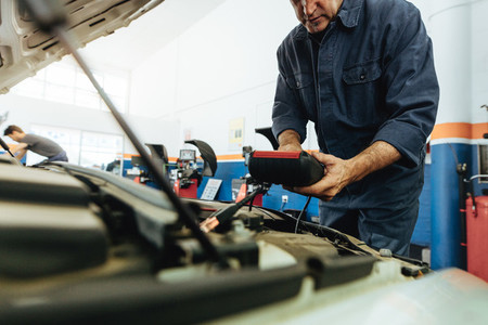 Technician using electronic equipment to diagnose the car