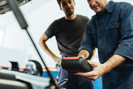 Mechanics using a device for checking engine