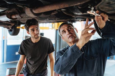 Two mechanics repairing a car