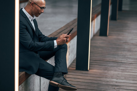 Businessman using mobile phone sitting outdoors