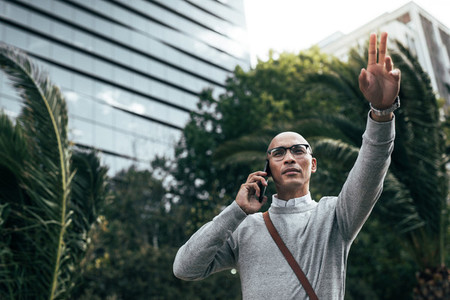 Man talking on mobile phone outdoors calling out to somebody