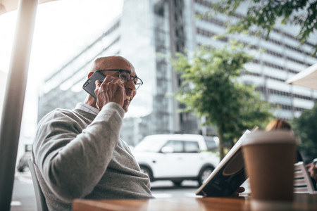 Businessman talking on mobile phone sitting at a restaurant