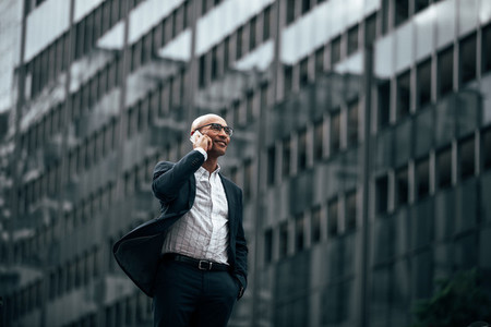 Businessman standing outdoors talking over mobile phone