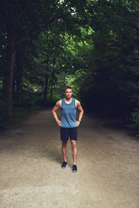 Athletic young man standing waiting in a park