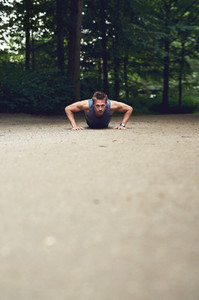 Fit young man doing push ups in a park