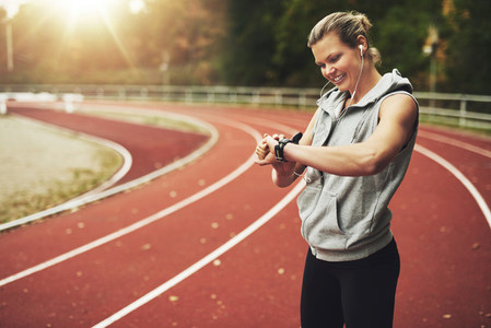 Young sportswoman looking at her watch while standing on track field
