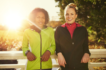 Two smiling sportswomen leaning on bridge and looking at camera