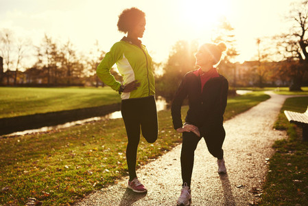 Two female athletes stretching in park