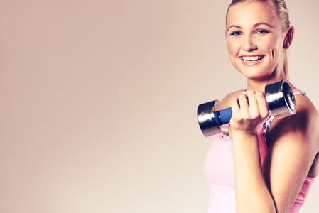 Woman smiling at camera and holding dumbbell