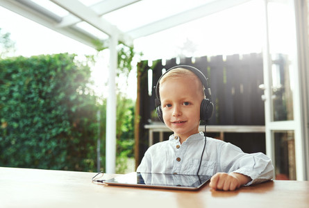 Cute smiling little boy listening to his music