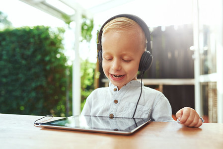 Happy laughing little boy listening to music