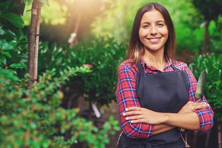 Smiling happy young woman enjoying her garden