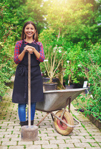 Smiling young woman transplanting nursery stock