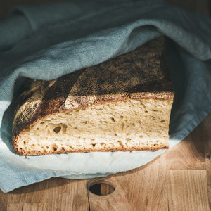 Rustic French rye bread loaf covered with kitchen towel