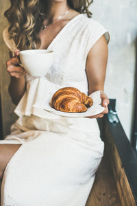 Blond woman holding fresh croissant and cup of cappuccino