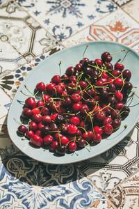 Fresh sweet cherries over oriental ceramic tiles background