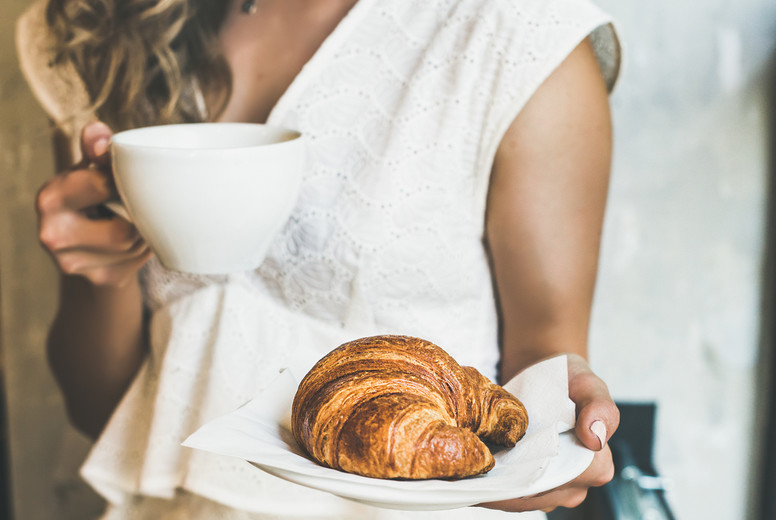 Blond woman holding croissant and cappuccino in cafe  square crop