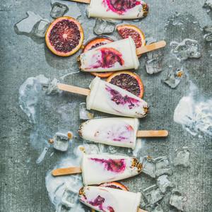 Red orange  yogurt  granola popsicles on ice cubes  square crop
