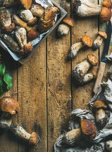 Freshly picked white forest mushrooms leaves knife on wooden background