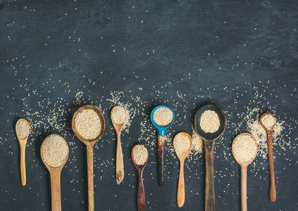 Quinoa seeds in spoons over black stone background copy space