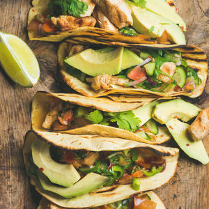 Close up of tacos with chicken avocado fresh salsa and limes
