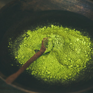 Japanese Matcha green tea powder in wooden bowl square crop