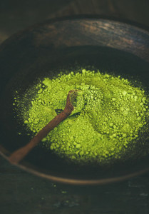 Japanese Matcha green tea powder in dark wooden bowl