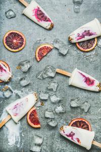 Blood orange  yogurt and granola popsicles on ice  grey background
