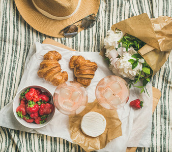 Flat lay of rose wine strawberries croissants brie cheese flowers