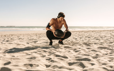 Man training at the beach using a medicine ball listening to mus