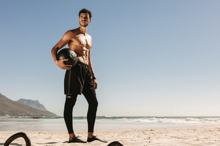 Man doing fitness training at the beach using a medicine ball