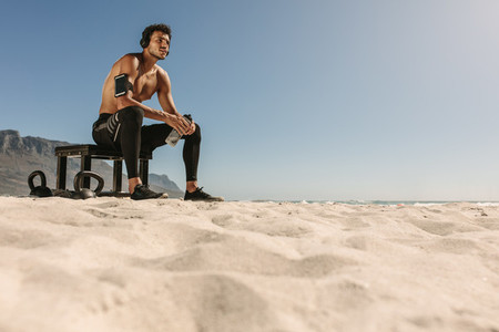 Man relaxing after workout on the beach drinking water
