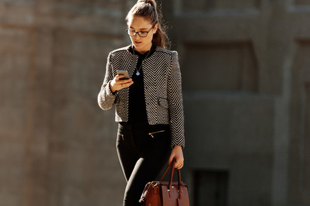 Businesswoman using mobile phone while commuting to office