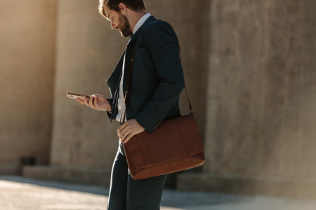 Man using mobile phone while commuting to office