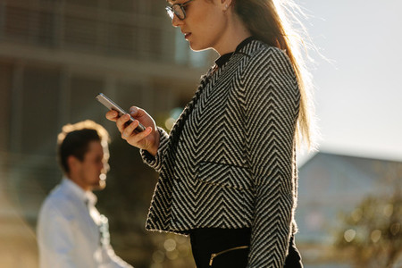 Businesswoman using mobile phone while walking on street to offi